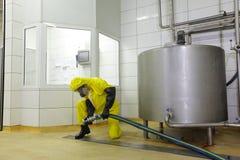 Technicien avec le grand tuyau au réservoir industriel à l'usine image libre de droits