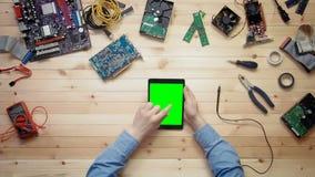 Technicien d'ordinateur de vue supérieure à l'aide du comprimé numérique avec l'écran vert au bureau en bois avec des outils et d banque de vidéos
