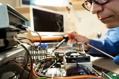 Technicien d'ordinateur réparant le matériel avec des outils Photos stock