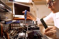 Technicien d'ordinateur réparant le matériel avec des outils Images libres de droits