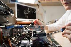 Technicien d'ordinateur réparant le matériel avec des outils Photographie stock