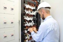 Technicien dans la boîte de communications reliant les fibres optos images libres de droits