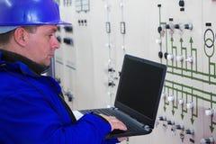 Technicien dans le bleu avec des instruments de lecture d'ordinateur portable dans le plan de puissance Photographie stock libre de droits