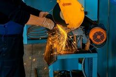 Technicien dans les gants et combinaisons dans le lieu de travail Coupure du métal avec une machine dans le magasin image libre de droits