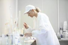 Technicien de laboratoire féminin faisant des essais dans un laboratoire dans un c industriel image stock