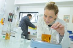 Technicien de laboratoire pesant le flacon en verre contenant du liquide photo stock