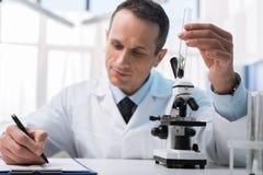 Technicien de laboratoire prenant des notes image stock