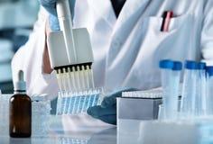 Technicien de recherches avec le multipipette dans le laboratoire génétique image libre de droits