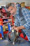 Technicien de tronçonneuse fixant la scie électrique Photos stock