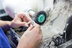 Technicien dentaire polissant une prothèse image libre de droits
