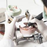 Technicien dentaire travaillant avec l'articulateur image libre de droits