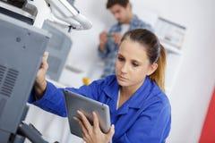 Technicien féminin travaillant au photocopieur tenant le comprimé images stock