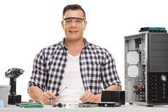 Technicien gai de PC réparant un ordinateur photographie stock libre de droits