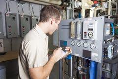 Technicien inspectant le système de chauffage dans la chaudière Photos libres de droits