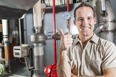 Technicien inspectant le système de chauffage dans la chaudière Image stock