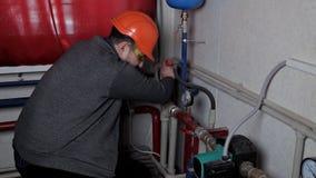 Technicien inspectant le système de chauffage dans la chaufferie banque de vidéos