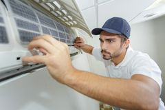 Technicien masculin de mi-adulte de portrait réparant le climatiseur photos stock