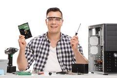 Technicien masculin de PC tenant une pièce d'ordinateur photographie stock