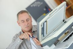 Technicien masculin mûr réparant la machine numérique de photocopieur photo libre de droits