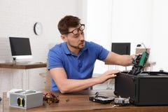 Technicien masculin r?parant l'ordinateur ? la table images libres de droits