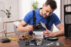 Technicien masculin r?parant l'unit? d'alimentation d'?nergie ? la table photos stock