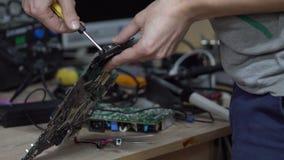 Technicien tenant la carte mère dans les mains Entretien dans l'atelier banque de vidéos