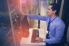 Technicien travaillant sur le PC tout en analysant le serveur Photographie stock