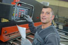 Technicien usando o dispositivo eletrónico na fábrica imagens de stock