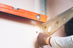 Technicien using Clinometer Bubble Level Ruler tool to install r royalty free stock photography