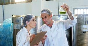 Techniciens écrivant sur le presse-papiers tout en examinant l'huile d'olive 4k banque de vidéos