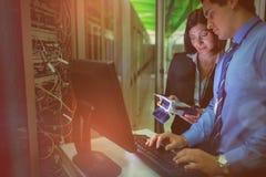 Techniciens employant l'analyseur numérique de câble tout en travaillant sur le PC Photos libres de droits