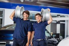 Techniciens portant les alliages métalliques sur des épaules Image libre de droits