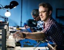 Techniciens travaillant aux pièces de l'électronique images libres de droits