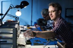 Techniciens travaillant aux pièces de l'électronique d'ordinateur image stock