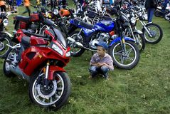 Technics miracle. The boy with admiration considers a red motorcycle Stock Image