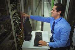 Technicus die aan personal computer werken terwijl het analyseren van server royalty-vrije stock foto's