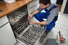 Technicus die afwasmachine herstellen stock foto's
