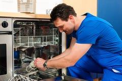 Technicus die de afwasmachine herstelt royalty-vrije stock fotografie