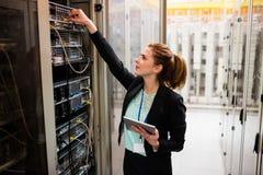Technicus die digitale tablet houden terwijl het onderzoeken van server stock foto