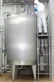 Technicus die industrieel proces in tank controleert Stock Afbeelding