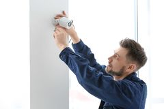 Technicus die kabeltelevisie-camera binnen installeren op muur royalty-vrije stock afbeelding
