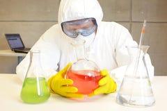 Technicus die in laboratorium met chemische producten werken Stock Foto's
