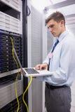 Technicus die laptop met behulp van terwijl het analyseren van server Royalty-vrije Stock Foto