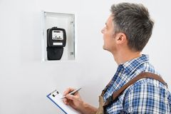 Technicus die lezing van elektrische meter nemen stock afbeeldingen
