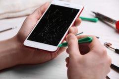 Technicus die mobiele telefoon bevestigen bij lijst, close-up royalty-vrije stock foto