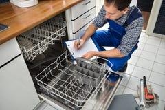 Technicus die op klembord in keuken schrijven stock foto's