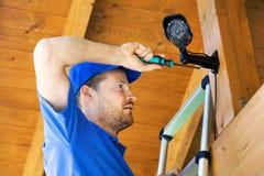 Technicus die toezichtcamera installeren in het huis carport stock fotografie
