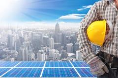 Technicus en zonne-energiepanelen bij de hoge bouw tegen galant Royalty-vrije Stock Foto's