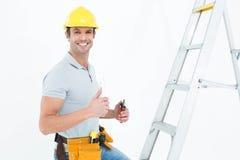 Technicus met hulpmiddelen die duimen tonen door stapladder Stock Foto's