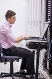 Technicuszitting op draaistoel die laptop met behulp van om servers te diagnostiseren stock afbeeldingen
